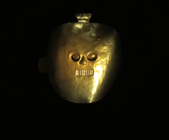 Golden indigenous mask from South America with black background